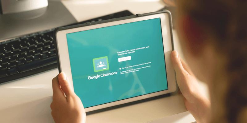 Imagem de uma pessoa segurando um tablet que mostra a tela inicial do Google Classroom
