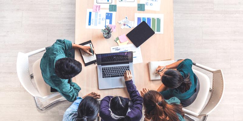 ´Foto vista de cima de grupo de pessoas em uma mesa com notebooks e diversos papéis