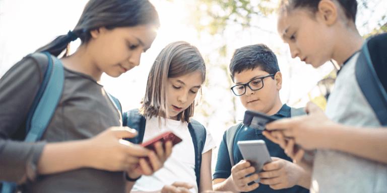 Alunos reunidos com celular na mão, representação da educomunicação