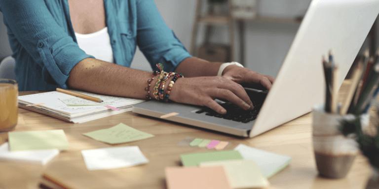 Imagem de professora usando notebook em mesa com vários papéis